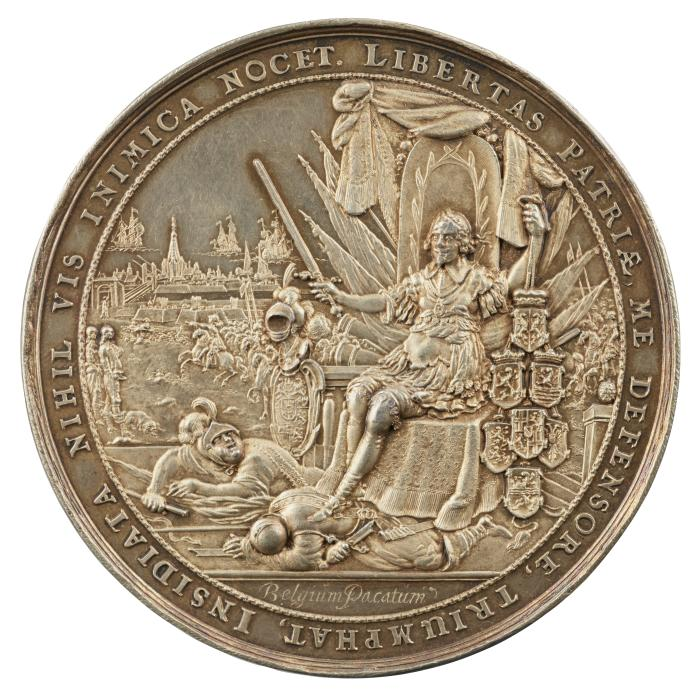Silver medal of a man sitting upon a throne wearing classical armor and holding a sword in his right hand