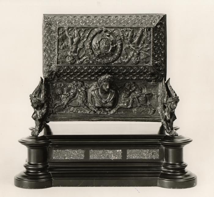 Bronze casket with protruding head in the middle at the back and various intricate motifs throughout.  There is a crest in the center with two putti at either side on the lid.