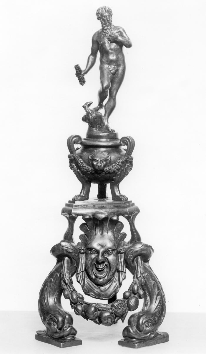 A bronze firedog with a figure of Jupiter.  He has his left hand up to his chest, and has curly hair and a long beard.  There is an eagle at his feet, his right foot is propped on top of it.