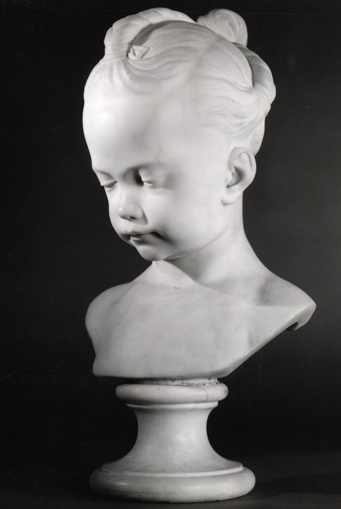 Marble bust of a young girl.  Her head and eyes are tilted downward, she has her hair twisted in three sections that meet at a bun in the back of her head.