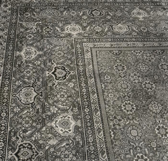 Black and white image of corner portion of Persian carpet with floral design