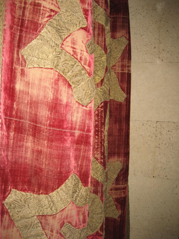 Red velvet hanging with woven design against stone background