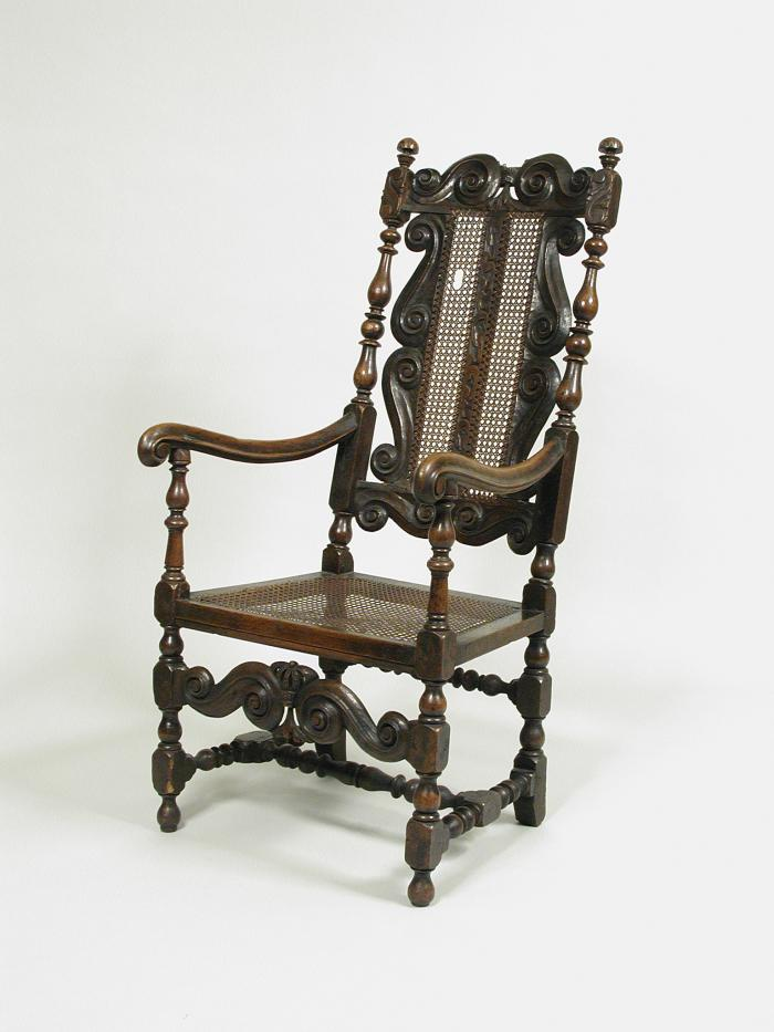 Walnut armchair with scrollwork decoration and woven seat