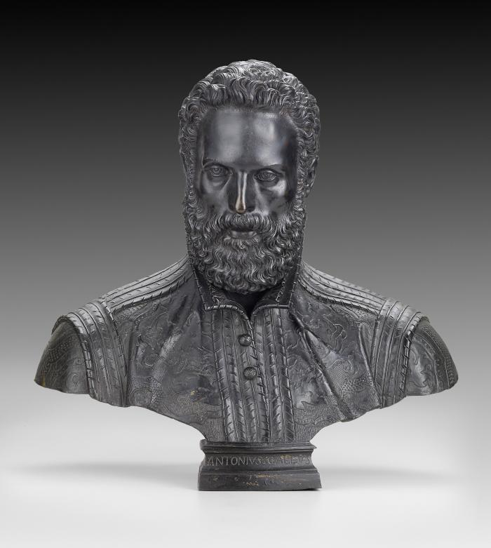 A bronze sculpture of Antonio Galli.  His eyes are facing straight ahead, he has curly hair and is bearded. He wears a carefully detailed costume, which features a brocaded doublet, stiff collar framing a ruffled shirt, and woven buttons.