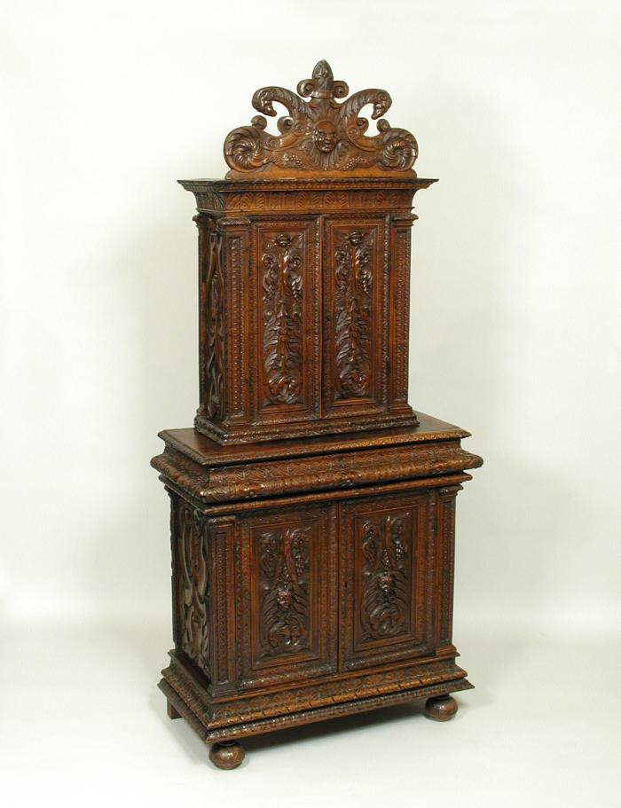 Walnut and pine cabinet with relief carving of masks and vegetal motifs