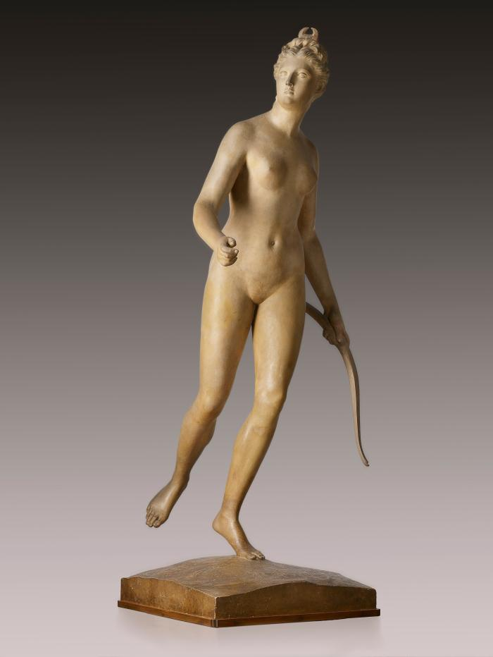 A terracotta sculpture of Diana.   She stands on the ball of her left foot, her right foot is extended behind her.  She looks to the right and holds a bow in her left hand, her right hand is positioned as if holding an arrow which is no longer part of the sculpture.