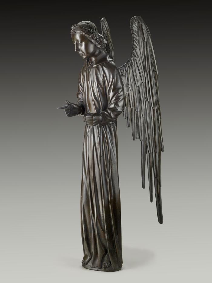 A bronze sculpture of an angel.  The angel stands upright with wings stretched behind it, the right pointer figure is pointing out and the angel glances downward.