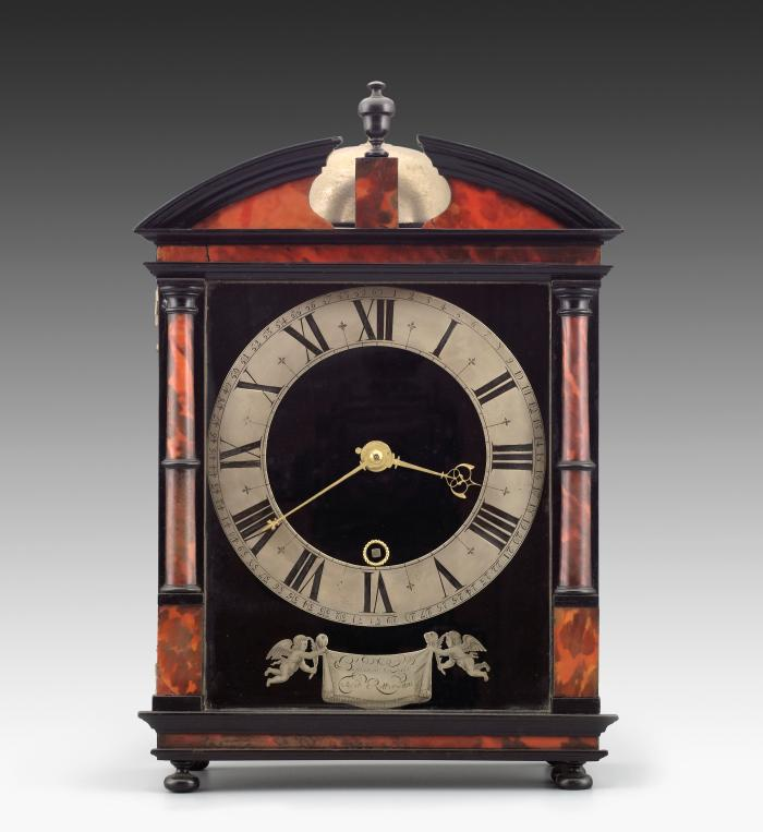Front view of Hague Clock with silver dial set against an architectural case made of veneered tortoiseshell and ebonized wood