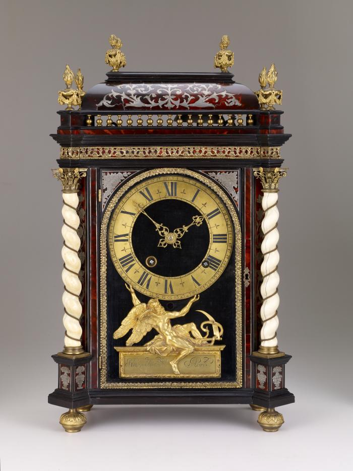 Front view of Mantel Clock, consisting of a luxurious mix of materials, including a gilt bronze dial held up by a figure of time in the same material, ivory twist pillars on the corners and glit bronze fire urns crowning a marqueted tortoiseshell and pewter case