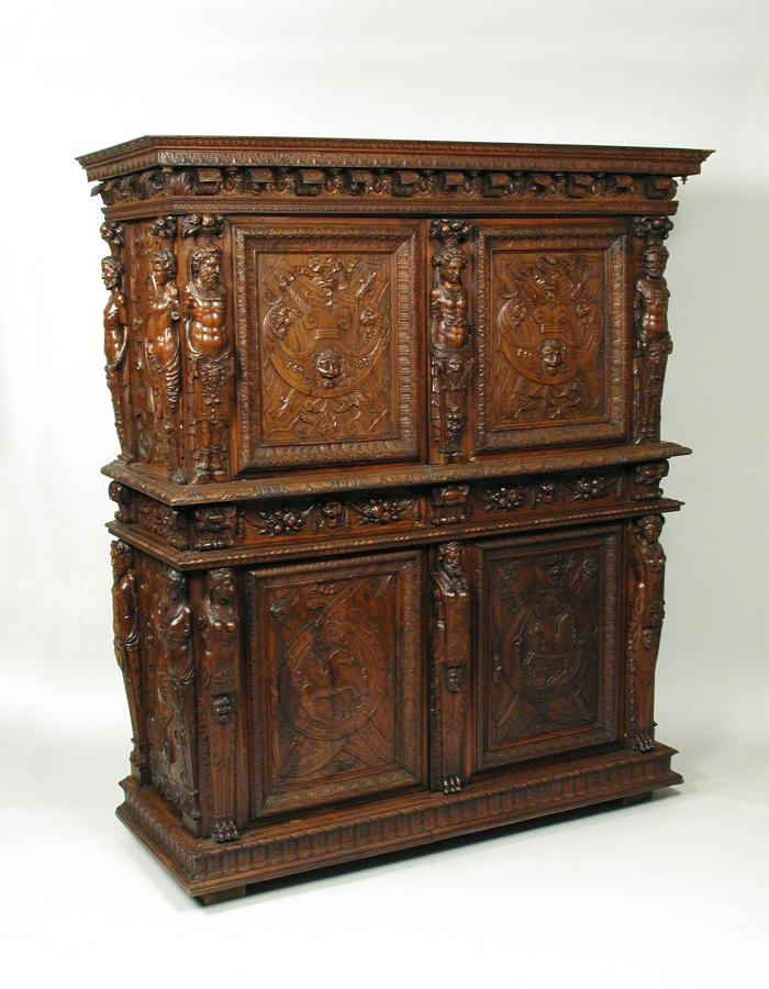 Walnut and pine cabinet with relief carving of trophies, masks, figural decoration, and vegetal motifs