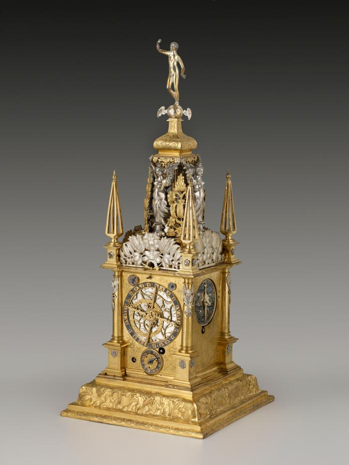 Three-quarter frontal view of Table Clock with Astronomical and Calendrical Dials, lavishly decorated in silver and gilt bronze, including a female figure surmounting the clock, standing on a base supported by four winged female figures in silver
