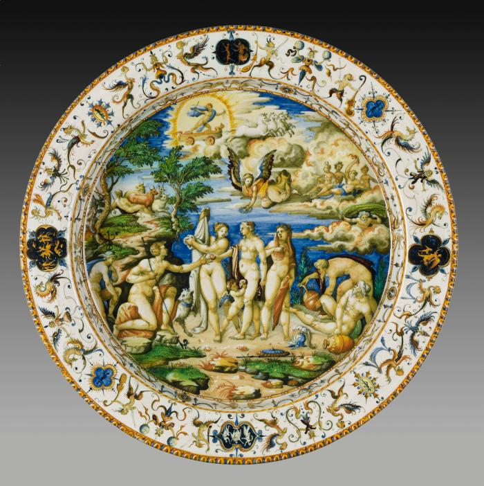 Ceramic dish representing in the middle a group of nude male and female figures against a country landscape. The thick white border decorated by arabesque decoration