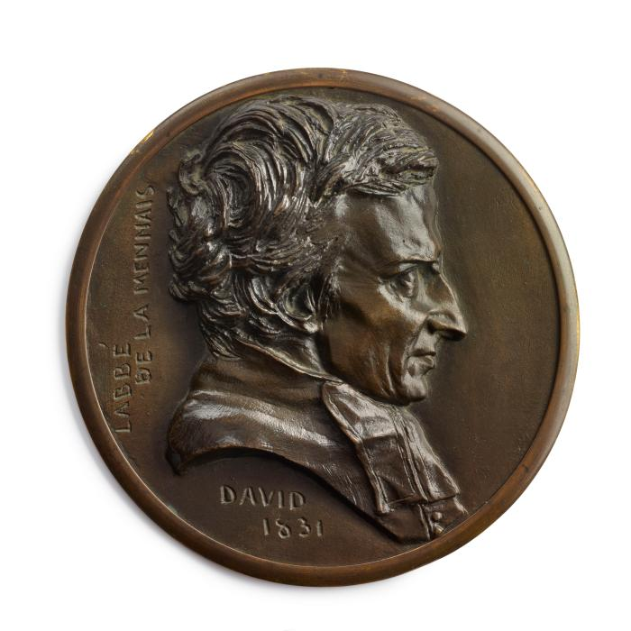A bronze circular medal.  The sitter is L'Abbé de Lamennais, he is seen in profile from his right side.  He has a full head of hair and and wears a high collared jacket with a scarf.