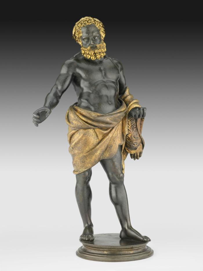 Bronze sculpture of Hercules.  He stands upright, his right arm is stretched out to his side, and his right hand is positioned as if holding a club that is longer part of the sculpture.  He has a golden lion's pelt wrapped around his torso, his short curly hair and beard are gilded and he has silver inlaid eyes.