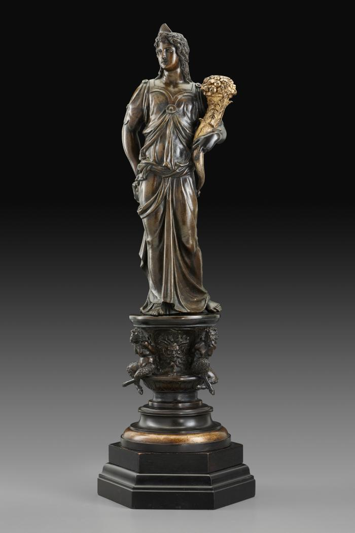 A bronze sculpture of a female figure with a cornucopia.  Her head is turned to her right and she cradles a golden cornucopia in her left arm.