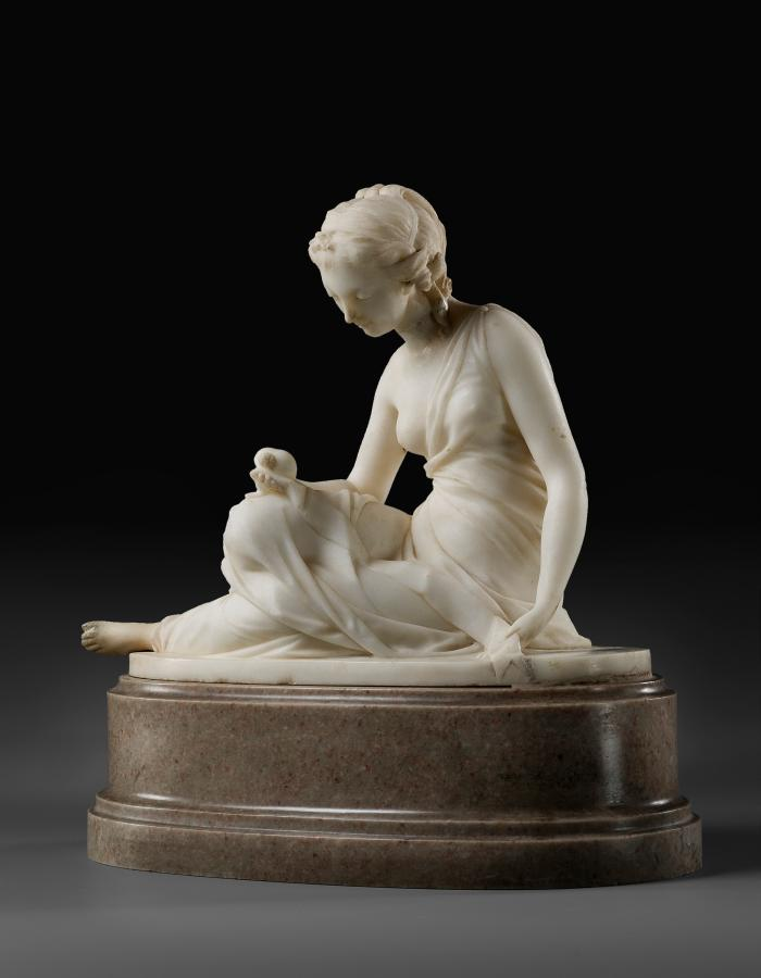 Marble sculpture of Friendship.  She is sitting down with her legs stretched out to her right side.  She is looking down and examining something in her right hand, which rests on her right knee.