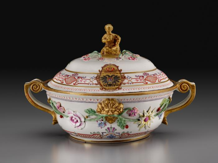 White porcelain lidded tureen with gilded handles decorated with garlands of flowers