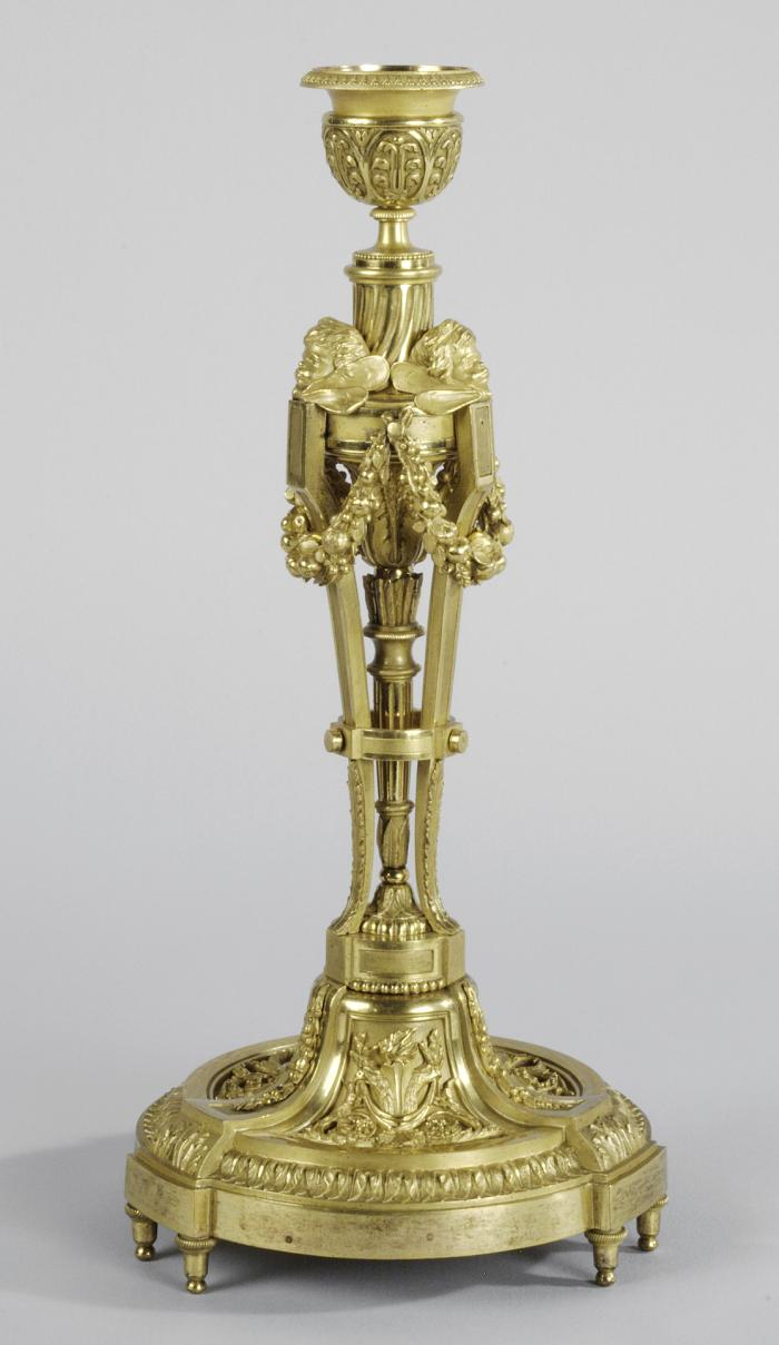 Gilt bronze candlestick with cherub heads and swags of garland
